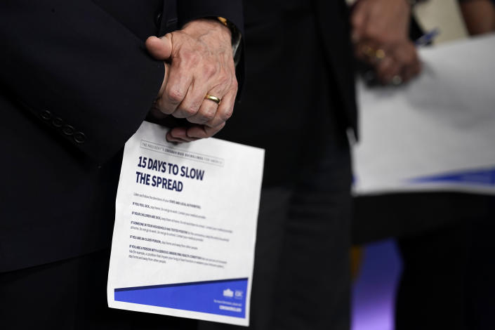 Vice President Mike Pence holds a information sheet during a press briefing with the coronavirus task force, in the Brady press briefing room at the White House, Monday, March 16, 2020, in Washington. (AP Photo/Evan Vucci)