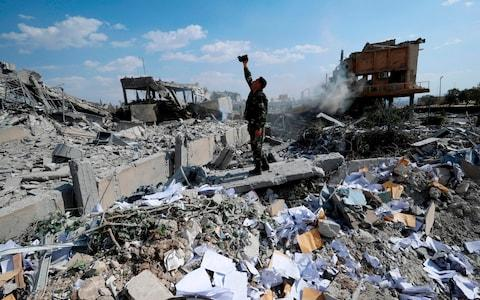 A Syrian soldier films the damage of the Syrian Scientific Research Center which was attacked by U.S, British and French military strikes - Credit: AP