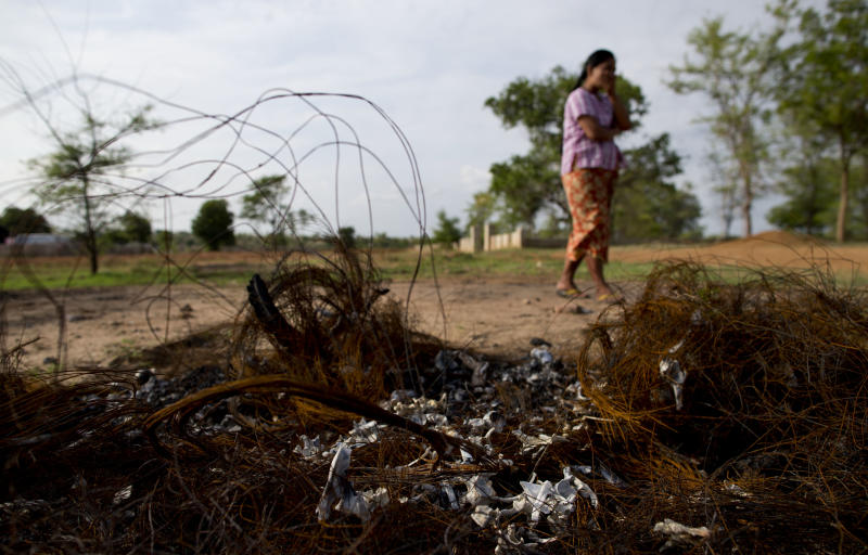 In this May 24, 2013 photo, a pile of burned car tires and human bones from the Meikhtila massacre rest in foreground as the local cemetery caretaker, Khin Mar Cho stands nearby. Twenty-five Buddhists were sentenced to as many as 15 years in prison for murder and other crimes during a night of rioting, burning and killing in central Myanmar, following weeks in which it seemed only Muslims were being punished for sectarian violence that was aimed primarily at members of their own religion. But the sentences issued Wednesday and Thursday, July 11. 2013, did not erase a sense of unequal justice: A day earlier, a Muslim received a life sentence for murdering one of the 43 people killed March 20 and 21 in the central Myanmar town of Meikhtila. (AP Photo/Gemunu Amarasinghe)