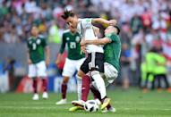 <p>Mesut Oezil of Germany is tackled by Hector Herrera of Mexico during the 2018 FIFA World Cup Russia group F match between Germany and Mexico at Luzhniki Stadium on June 17, 2018 in Moscow, Russia. (Photo by Hector Vivas/Getty Images) </p>