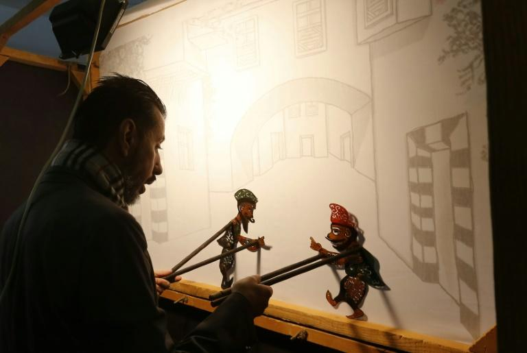 Syria's last shadow puppeteer Shadi al-Hallaq is seen moving his puppets Karakoz (R) and Eiwaz (L) from inside his booth during a presentation in Damascus