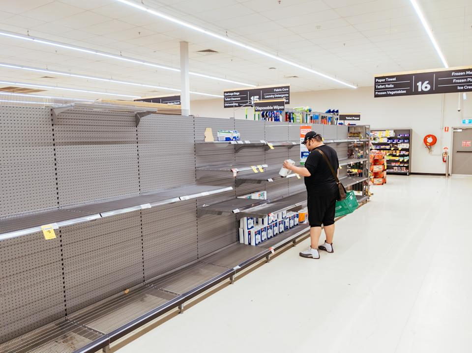 MELBOURNE, AUSTRALIA - MARCH 4, 2020: A man looks for toilet paper in an Australian supermarket after panic buying due to the Corona Virus