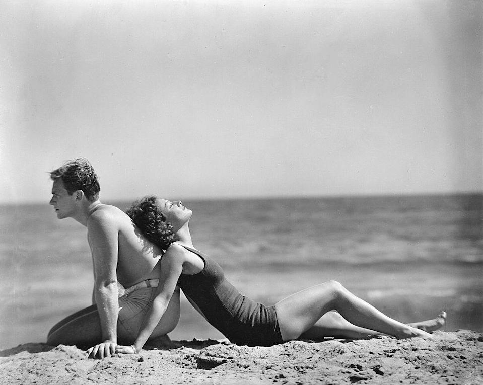 <p>Joan Crawford leans on husband Douglas Fairbanks Jr. while taking it easy in the sand.</p>