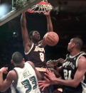 Los Angeles Lakers' Kobe Bryant, playing for the West All-Stars, reacts to his dunk over Detroit Pistons' Grant Hill and San Antonio Spurs' Tim Duncan, right, in the first half of the NBA All-Star game at New York's Madison Square Garden on Sunday, Feb. 8, 1998. (AP Photo/Mark Lennihan)