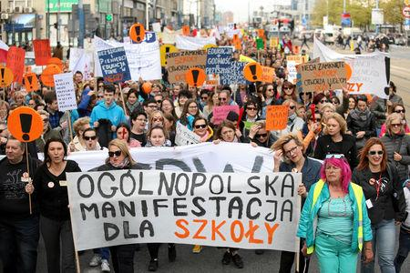 """People hold banners during a rally to support a nationwide teachers' strike in central Warsaw, Poland April 24, 2019. Banner reads """"Nationwide demonstration for the school"""". Agencja Gazeta/Jedrzej Nowicki via REUTERS"""