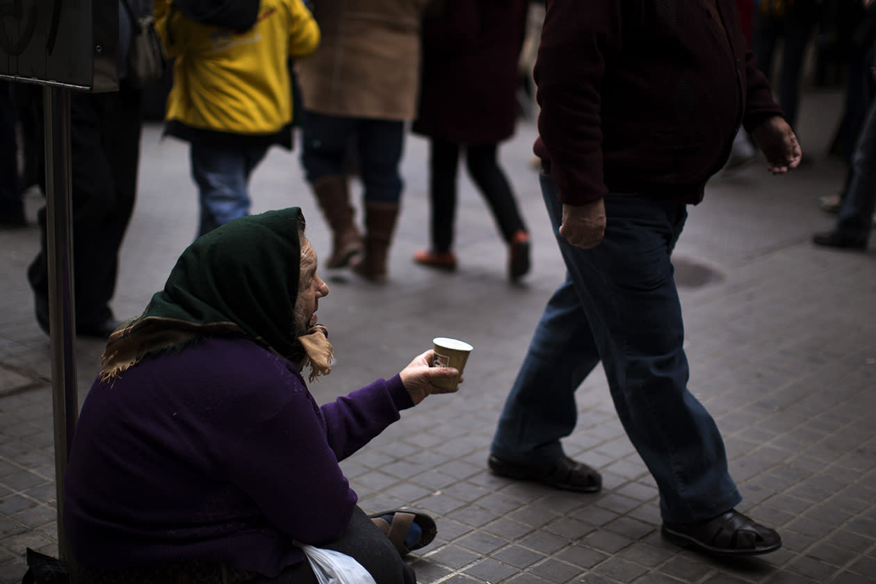 A woman begs for alms in a street in Barcelona.