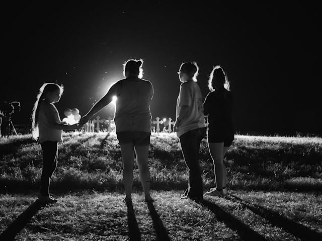 <p>A famlly stands near 26 crosses set up in a baseball field a few blocks from the site of Sunday's shooting during a memorial service on Monday nigth in Sutherland Springs, Texas. (Photo: Holly Bailey/Yahoo News) </p>