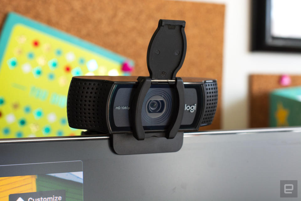 Logitech C920 HD Pro webcam clipped onto a computer monitor with cork boards hanging on the wall behind it.