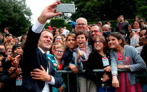 French President Emmanuel Macron (C) takes a 'selfie' with members of the crowd at the Mont Valérien national memorial in Suresnes near Paris - Credit: CHARLES PLATIAU/AFP