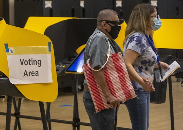Two voters wearing masks