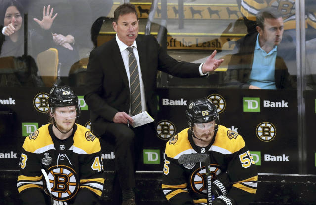 FILE - In this June 6, 2019, file photo, Boston Bruins head coach Bruce Cassidy, center, appeals to an official from the bench during Game 5 of the NHL hockey Stanley Cup Final against the St. Louis Blues in Boston. The Bruins are hoping to make a run at the Stanley Cup this season with essentially the same roster that made it to Game 7 of the finals last year. (AP Photo/Charles Krupa, File)
