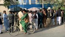 Afghans queue outside banks to withdraw cash from ATMs