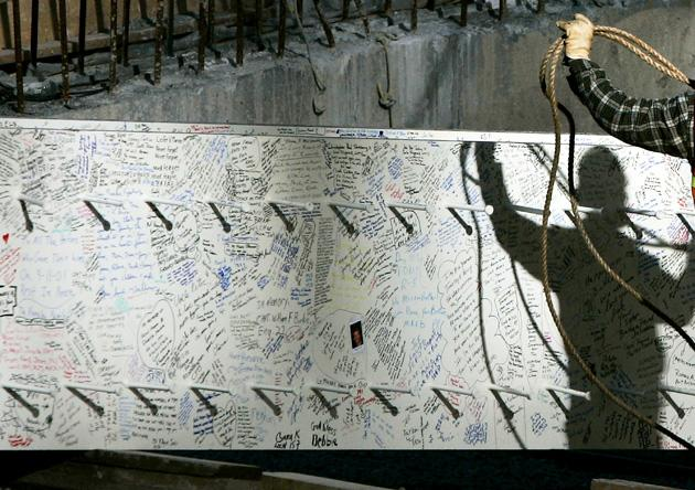 NEW YORK - DECEMBER 19:  A worker prepares to raise a steel beam signed by thousands of people that will be part of Freedom Tower at Ground Zero December 19, 2006 in New York City.  Several 25-ton steel beams were erected with fanfare at Ground Zero, marking the first vertical construction of the planned 1,776 foot tower at the site of the Twin Towers.  (Photo by Chris Hondros/Getty Images)