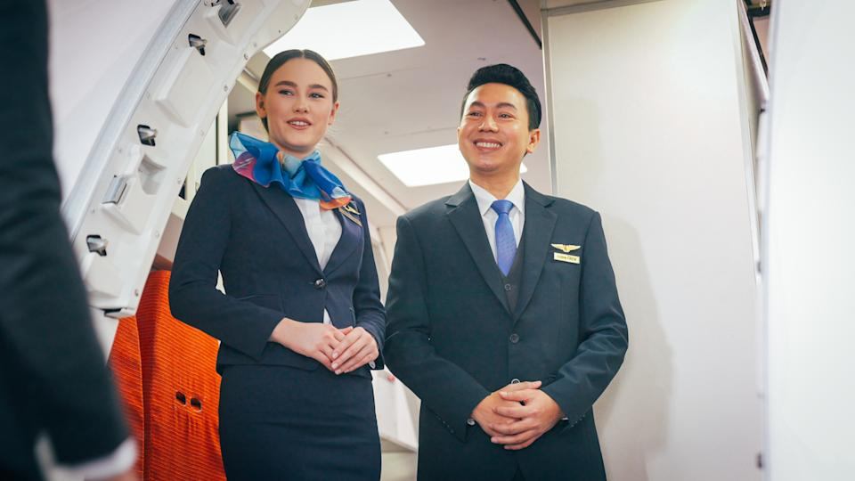 Air stewardess welcome in front of airplane