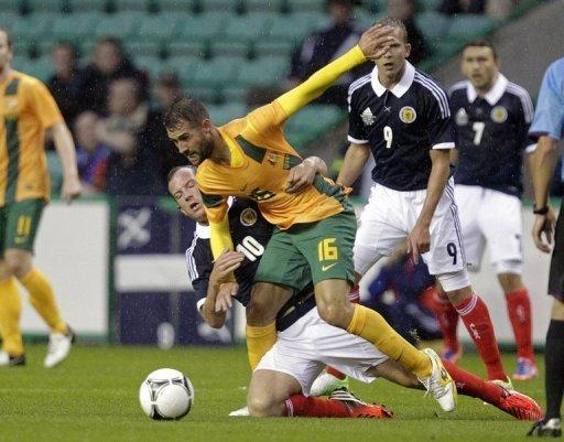 Charlie Adam (L) of Scotland vies with Australia's Carl Valeri (2nd L)