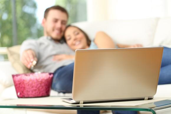 Young couple watching streaming laptop video on their couch, with a large bucket of popcorn close at hand.