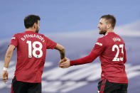 Manchester United's Luke Shaw celebrates with Bruno Fernandes, left, after scoring his side's second goal during the English Premier League soccer match between Manchester City and Manchester United at the Etihad Stadium in Manchester, England, Sunday, March 7, 2021. (Dave Thompson/Pool via AP)