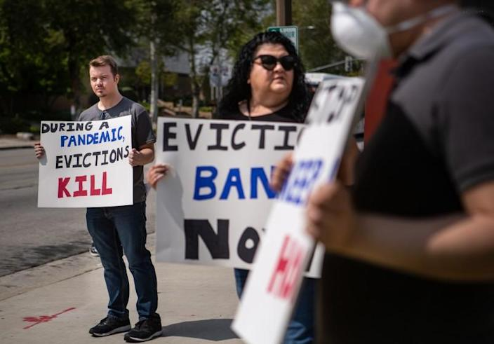 EL MONTE, CA - MARCH 29: Ian Jameson (left) of El Monte organized hold a sign along with other tenant rights activists assembled at the El Monte City Hall to demand that the El Monte City Council pass an eviction moratorium barring all evictions during the coronavirus pandemic on Sunday, March 29, 2020 in El Monte, CA. (Jason Armond / Los Angeles Times)