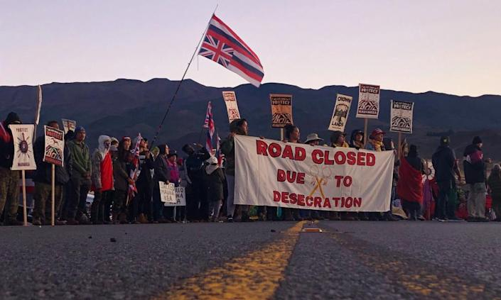 "<span class=""element-image__caption"">Demonstrators block a road at the base of Hawaii's tallest mountain, on 15 July.</span> <span class=""element-image__credit"">Photograph: Caleb Jones/AP</span>"