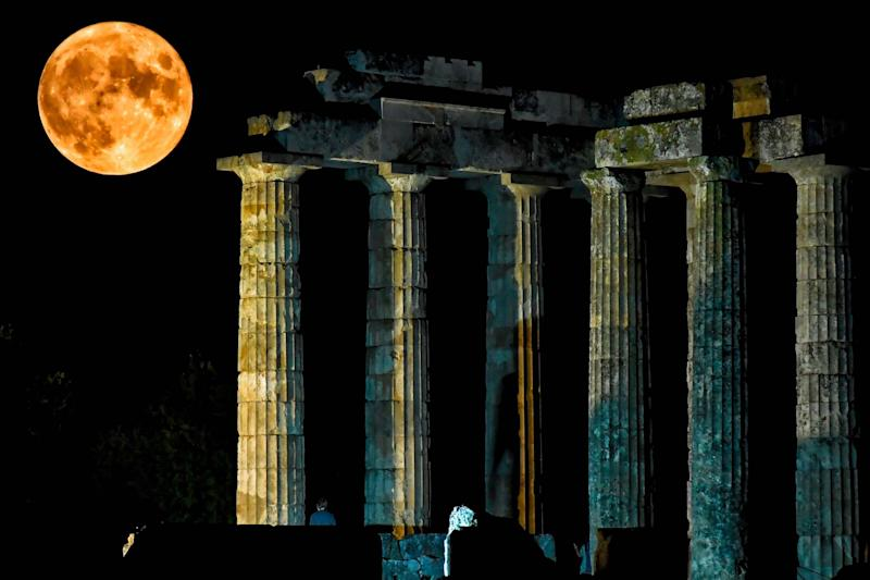 The full moon rises behind the ancient temple of Zeus in Nemea, Greece (AFP via Getty Images)