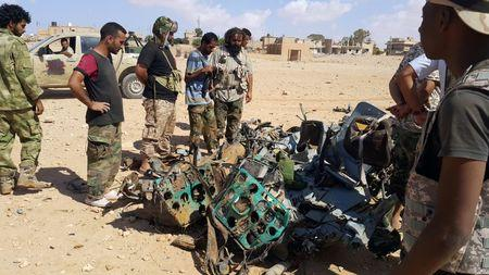 Libyans gather around the remains of a helicopter that crashed near Benghazi