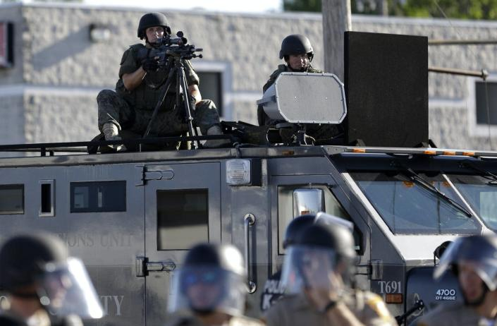 """<span class=""""caption"""">A police tactical team in Ferguson, Mo., responds to 2014 protests against a white officer's killing of Michael Brown, a young Black man.</span> <span class=""""attribution""""><a class=""""link rapid-noclick-resp"""" href=""""http://www.apimages.com/metadata/Index/Trump-Police-Military-Gear/5e071ec6710d4ec3a876fdec7cb13b78/2/0"""" rel=""""nofollow noopener"""" target=""""_blank"""" data-ylk=""""slk:AP Photo/Jeff Roberson"""">AP Photo/Jeff Roberson</a></span>"""