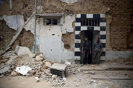 Two young men inspect damageson a building in the besieged town of Douma, eastern Ghouta, in Damascus