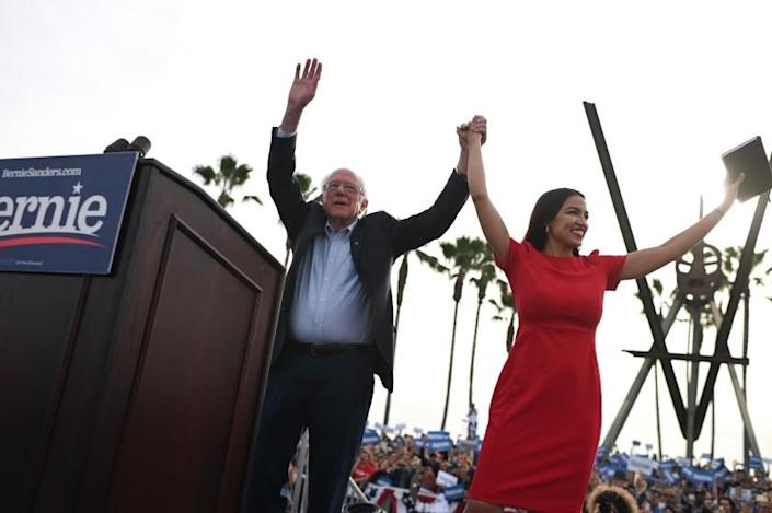 TOPSHOT - US Democratic presidential candidate Bernie Sanders (L) campaigns with Rep. Alexandria Ocasio-Cortez (D-NY) in the Venice Beach neighborhood of Los Angeles, California, December 21, 2019. (Photo by Robyn Beck / AFP) (Photo by ROBYN BECK/AFP via Getty Images)