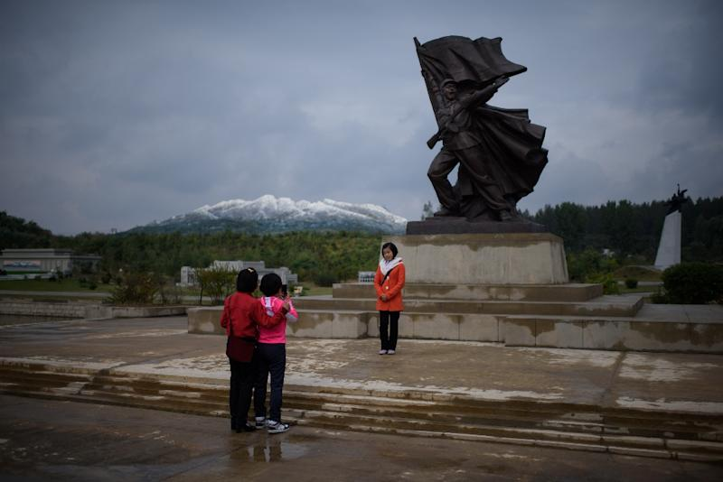 """North Korean youths pose before a model of Mount Paektu at a 'Folk Park' in Pyongyang, among a number of costly """"leisure"""" projects aimed at projecting prosperity (AFP Photo/Ed Jones)"""