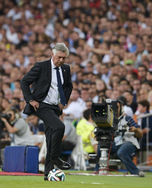 Real Madrid's Italian coach Carlo Ancelotti stops the ball during the Spanish Supercup first-leg football match Real Madrid CF vs Club Atletico de Madrid at the Santiago Bernabeu stadium in Madrid on August 19, 2014 (AFP Photo/Dani Pozo)