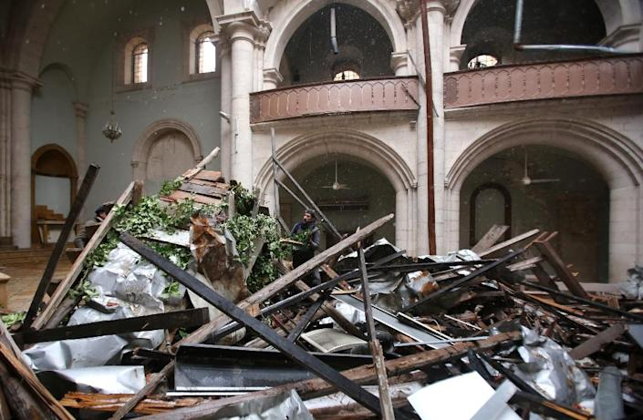 Members of the Saint Elias Cathedral committee inspect the damage inside the building in Aleppo's Old City on December 21, 2016 (AFP Photo/Youssef KARWASHAN)