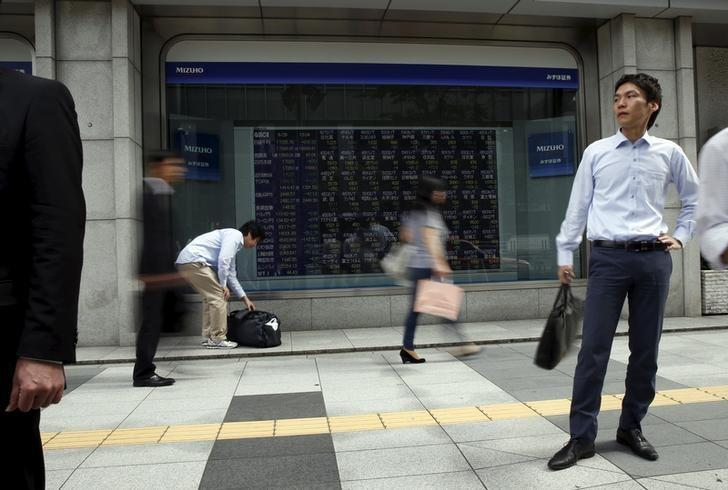 Passersby walk past in front of stock quotation board outside a brokerage in Tokyo