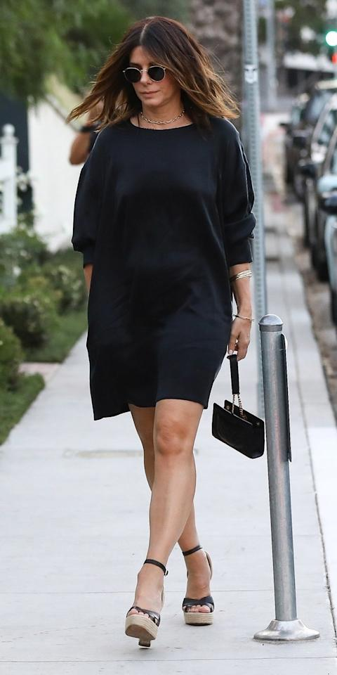 <p>Sandra Bullock elevated a shirt dress by pairing it with cute wedges, a leather handbag, gold necklace, and aviator shades.</p>