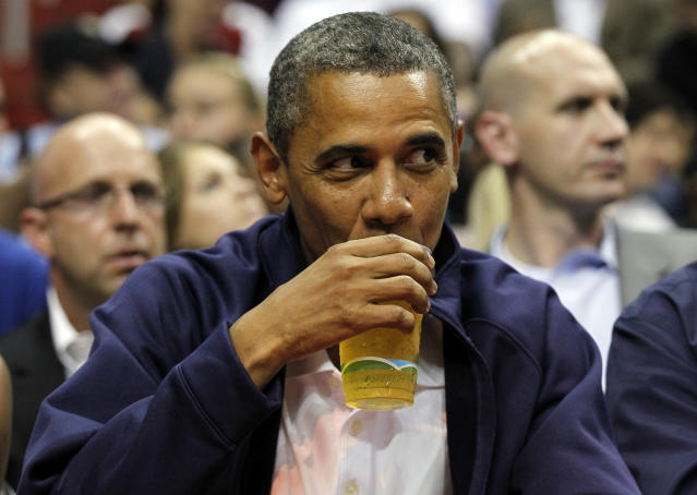 President Barack Obama sips his beer as he watches Team USA and Brazil during the first half of an Olympic men's exhibition basketball game, Monday, July 16, 2012, in Washington. (AP Photo/Alex Brandon)
