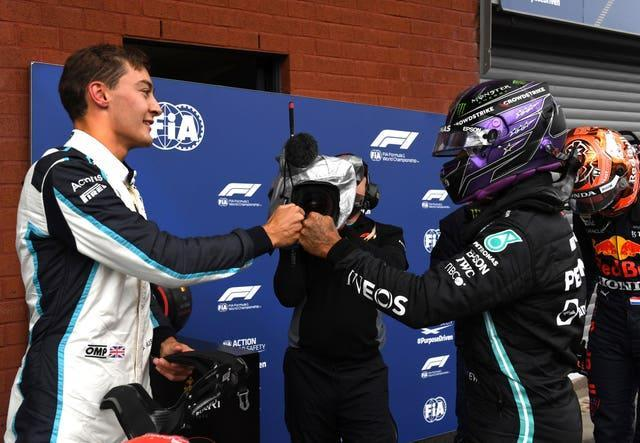 George Russell (left) fist-bumps Lewis Hamilton