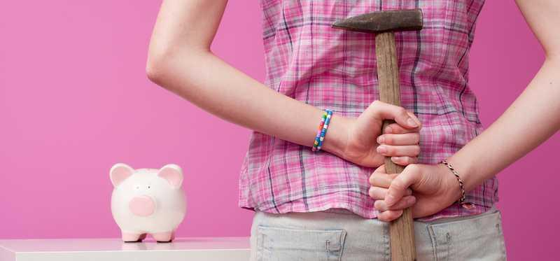 A woman yielding a hammer behind her back faces a piggy bank.