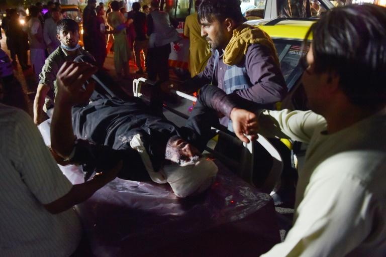 Medical and hospital staff bring an injured man on a stretcher for treatment after two blasts, which killed at least five and wounded a dozen, outside the airport in Kabul