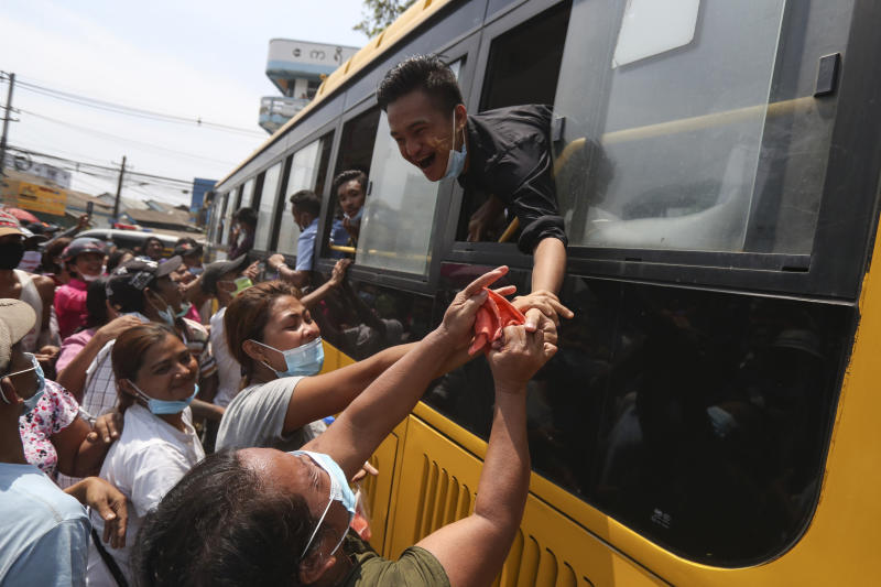 A prisoner reaches out from a bus to shake hands with family members after being released from the Insein prison during a presidential pardon in Yangon, Myanmar, Friday, April 17, 2020. Myanmar says it is releasing almost 25,000 prisoners under a presidential amnesty marking this week's traditional Lunar New Year celebration. (AP Photo/Thein Zaw)