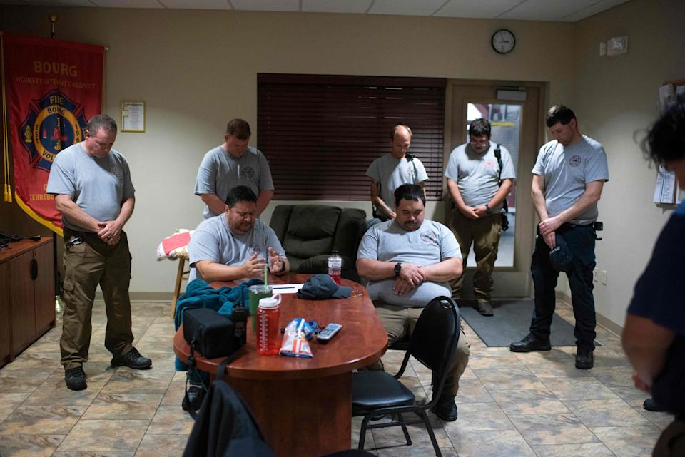 Firefighters sitting and standing around a conference table bow their heads with hands clasped.