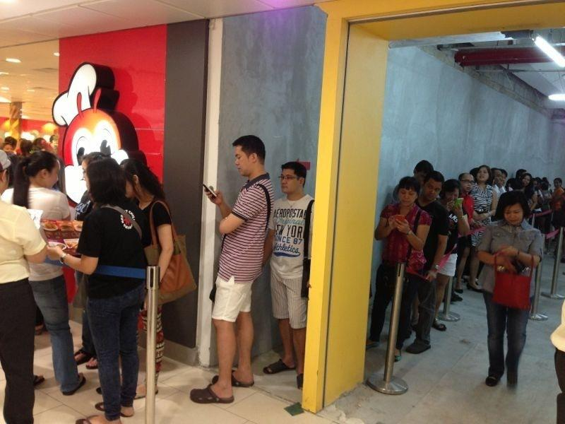 """Long queues form on the sixth floor of Lucky Plaza, along Orchard Road, as <a href=""""http://sg.entertainment.yahoo.com/news/filipino-fast-food-joint-jollibee-open-flagship-store-102836500.html"""" data-ylk=""""slk:Filipino fast food king Jollibee opens its first store in Singapore.;outcm:mb_qualified_link;_E:mb_qualified_link;ct:story;"""" class=""""link rapid-noclick-resp yahoo-link""""> Filipino fast food king Jollibee opens its first store in Singapore.</a>"""
