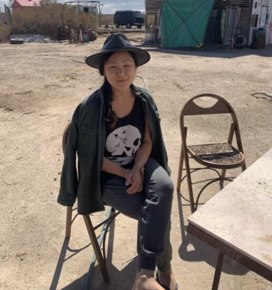 Lauren sitting on a chair wearing light colored pants, a dark tee-shirt with a skull on hit, and a fedora