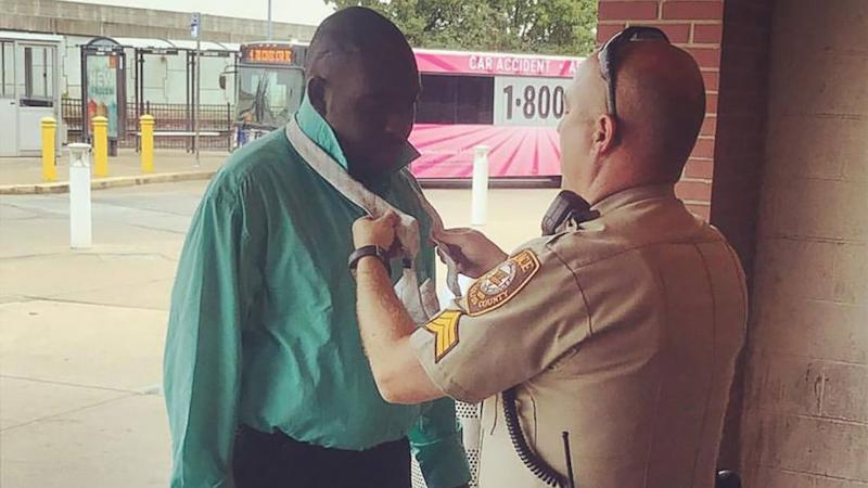 Police sergeant helps man tie his tie for job interview