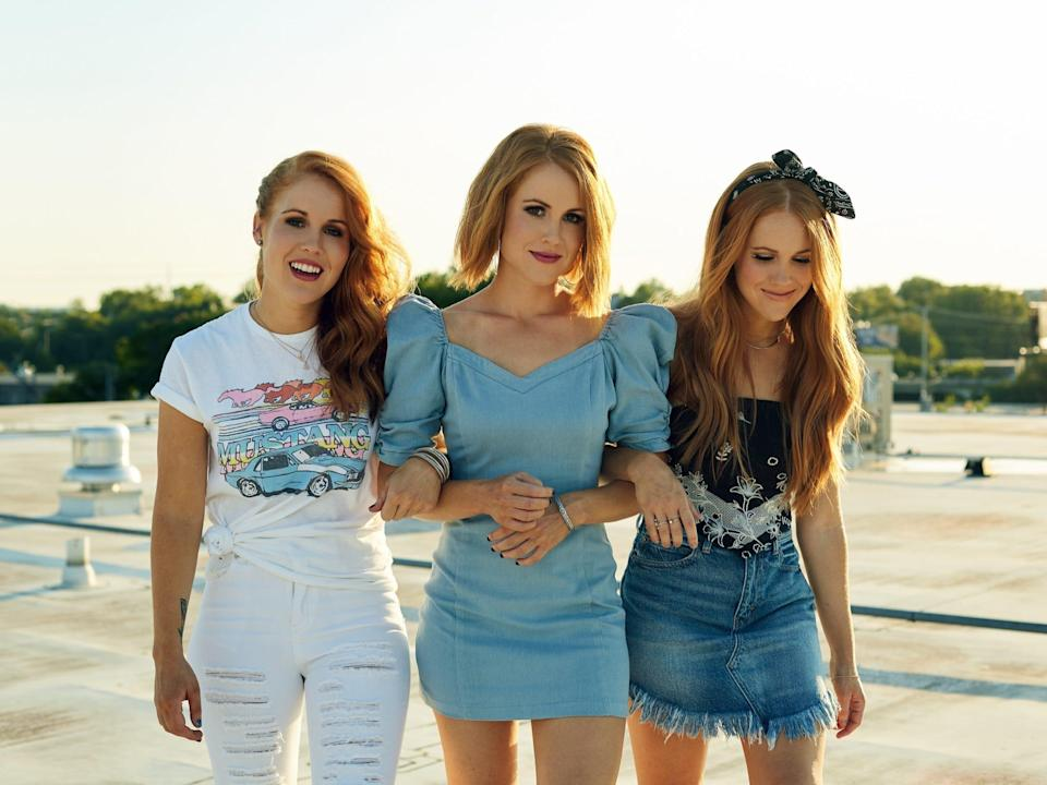 The music trio Taylor Red appear outside on a roof with their arms linked.