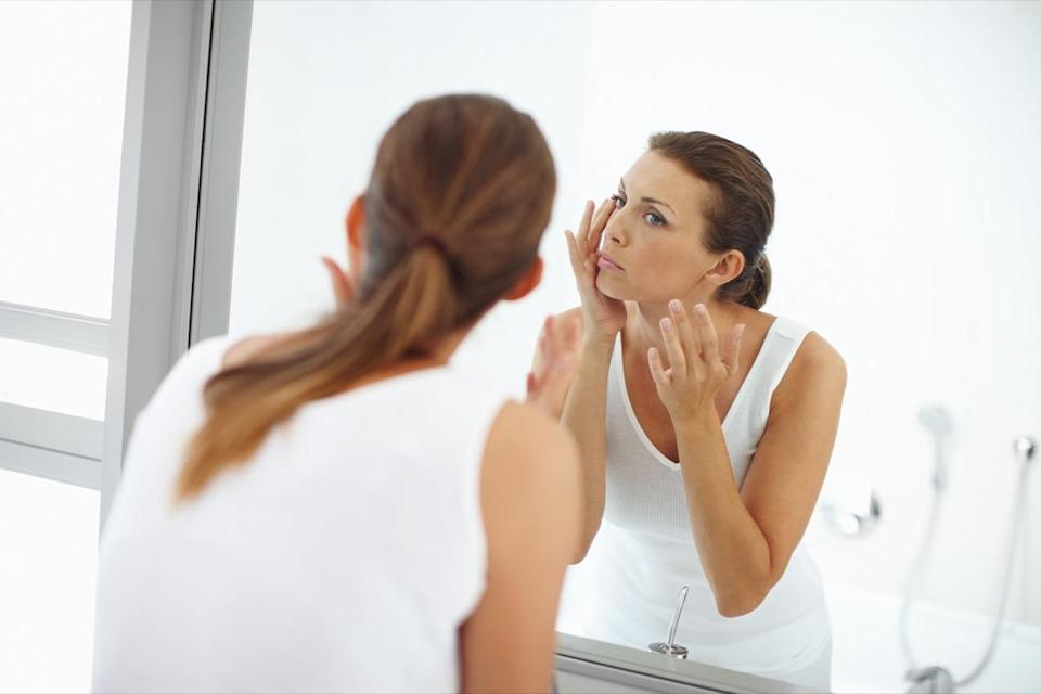 Woman applying lotion to the skin around her eyes in the mirror