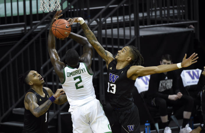 Washington forward Nate Roberts (1) and Washington forward Hameir Wright (13) defend against Oregon forward Eugene Omoruyi (2) who drives to the basket during the first half of an NCAA college basketball game Saturday, Feb. 6, 2021, in Eugene, Ore. (AP Photo/Andy Nelson)