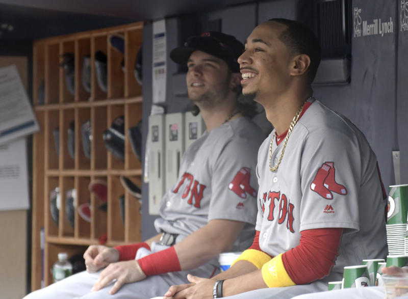 Red Sox outfielders Andrew Benintendi and Mookie Betts in the dugout. (AP)