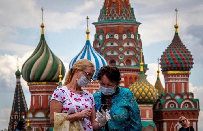 Two women wearing face masks to protect against the coronavirus stand in July 2020 in front of the Kremlin -- which the United States accuses of spreading conspiracy theories over the pandemic (AFP Photo/Yuri KADOBNOV)