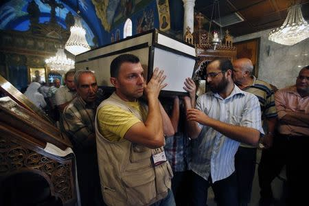 People carry a casket holding the body of Palestinian Christian woman Jalila Faraj Ayyad, whom medics said was killed in an Israeli air strike, during her funeral at the Saint Porfirios church in Gaza City July 27, 2014. REUTERS/Suhaib Salem