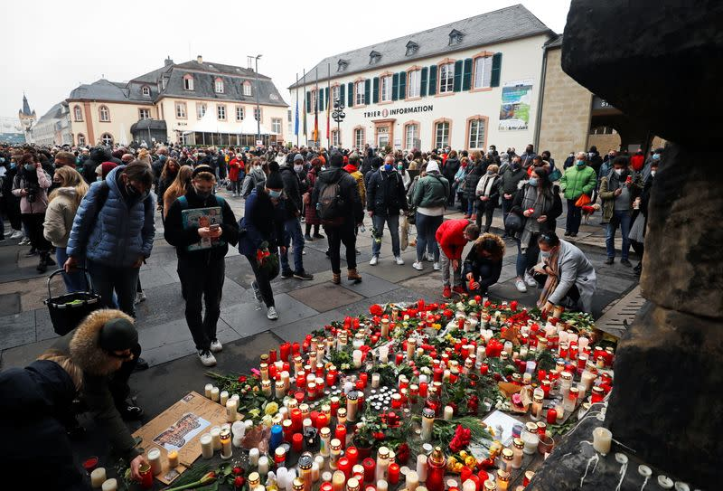 People pay their respects near the site where a car crashed into pedestrians in Trier