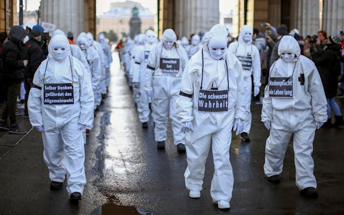 Protesters in white suits and wearing masks attend a demonstration against the Covid-19 restrictions in Vienna, Austria - Lisi Niesner/Reuters